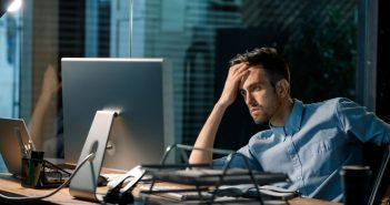 Ein Mann sitzt verzweifelt und ratlos an seinem Schreibtisch. Die Hand an der Stirn. Er scheint eine echte Krise zu durchleben.