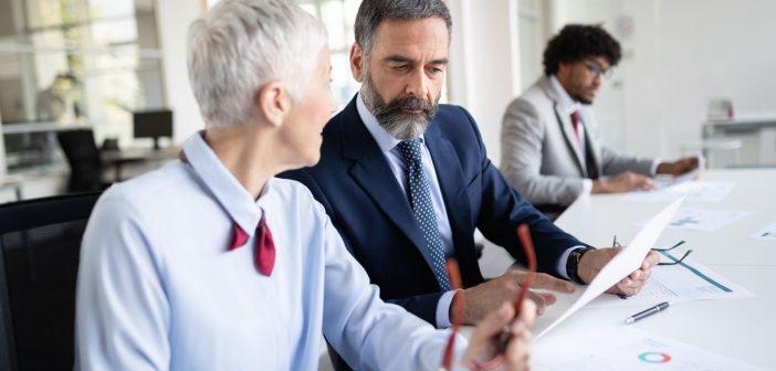 Ein Mann und eine Frau schauen sich Unterlagen im Büro an. Sind sie auf der Suche nach neuen Jobs?
