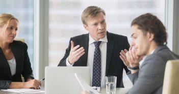 Eine Situation im Büro. In einem Meeting erläutert der Chef seine Sicht der Dinge. Er wirkt verärgert.