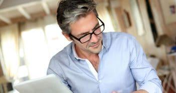 Ein Mann studiert aufmerksam Unterlegen. Womöglich schaut er sich gerade verschiedene Stellenanzeigen an.