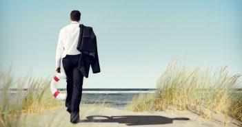 Ein Mann im Anzug läuft am Strand entlang. Auszeit vom Job, Urlaub oder Auszeit?