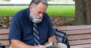 Ein älterer Mann sitzt auf einer Parkbank und liest Zeitung. Ob er einen neuen Job sucht, weil seine bisherige Karriere beendet ist?