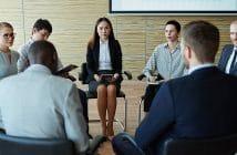 Eine Teamrunde: Die Mitarbeiter sitzen im Kreis zusammen und diskutieren.