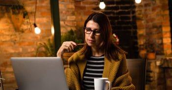 Eine Frau sitzt vor ihrem Laptop. Sie scheint über neue Ideen nachzudenken.