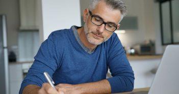 Ein Mann macht sich Notizen. Vielleicht plant er den Schritt zum Unternehmer.