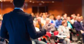 Ein Mann steht auf einer Bühne und spricht zum Publikum. Eine klassische Vortragssituation. Ob er schon als Marke bekannt ist?