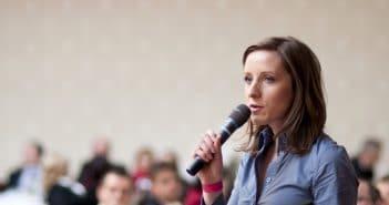 Eine Frau spricht in ein Mikrofon. Sie wirkt selbstsicher und präsent. Vielleicht der Erfolg einer Weiterbildung.