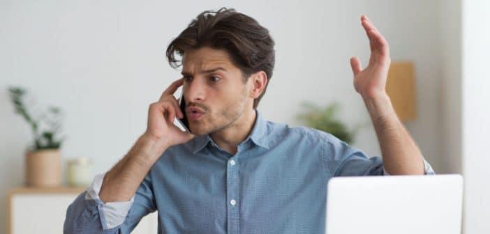 Ein Mann schreit wütend ins Telefon und gestikuliert wild mit seiner Hand.