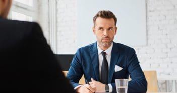 Ein Mann im Anzug in einem Bewerbungsgespäch.