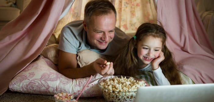 Ein Vater und seine Tochter sehen sich einen Film auf dem Laptop an. Sie essen Popcorn und wirken fröhlich.