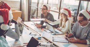 In einem Besprechungsraum haben die Angestellten schon die Weihnachtsmützen auf und stimmen sich auf den Jahresabschluss ein.