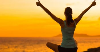 Eine Frau blickt im Schneidersitz in den Sonnenuntergang. Die Arme sind nach oben gestreckt, Daumen hoch.
