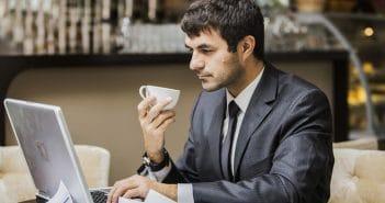 Ein Mann in den 40ern sitzt in einem Café und sucht im Internet nach Stellenanzeigen.
