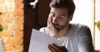 Schon wieder schlechte Nachrichten? Ein Mann starrt auf ein Blatt Papier und sieht ratlos aus.