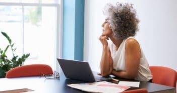 Eine Frau sinniert an ihrem Schreibtisch über Job-Alternativen.