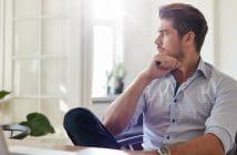 Ein junger Mann sitzt nachdenklich an seinem Schreibtisch. Grübelt er über seine Vorsätze fürs neue Jahr?