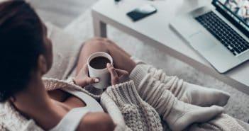 Eine Frau sitz in gemütlicher Kleidung eingekuschelt und mit einer Tasse Kaffee auf dem Sofa. Vor ihr auf dem Tisch steht der aufgeschlagene Laptop. Home Office kann ein Mittel sein, um mehr Zeit für sich zu haben.