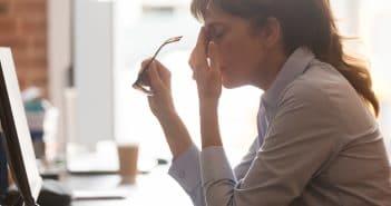 Eine Frau sitzt am Schreibtisch. Sie hält die Hand an die Stirn, hat ihre Brille abgenommen. Steckt sie in einer Krise?