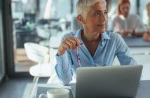 Ältere Frau sitzt vor ihrem Laptop, ihre Brille hat sie in der Hand. Sie hat nur noch wenige Jahre bis zur Rente.