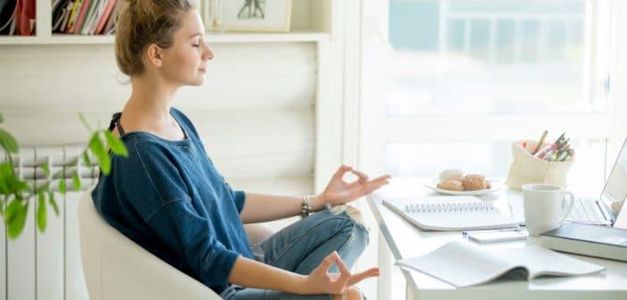 Eine junge Frau sitzt im Schneidersitz auf ihrem Bürostuhl am Schreibtisch und meditiert. Sie übt sich in Achtsamkeit.