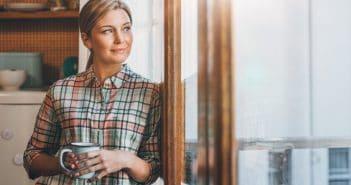 Eine Frau steht an einem Fenster, eine Kaffeetasse in der Hand. Sie schaut zuversichtlich nach draußen. Sieht sie neue Chancen für sich?