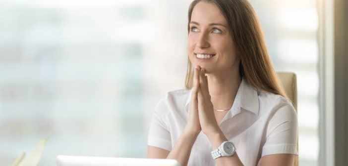 Die ersten Lockerungen in der Corona-Krise treten in Kraft. Zeit, einen mentalen Neuanfang zu starten. Die Frau auf dem Bild sitzt im Büro und sieht hoffnungsvoll in die Zukunft.