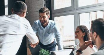 Zwei Männer schütteln sich die Hand, weil sie eine geschäftliche Einigung erreicht haben. Sie gestalten ihre Beziehung aktiv und kommunizieren miteinander.