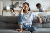 Eine Frau sitzt verzweifelt auf dem Sofa. Ihre Probleme haben sie fest im Griff.
