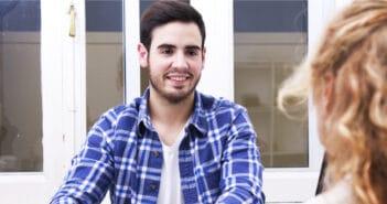 Ein junger Mann hat sich entschieden sich neu zu orientieren. Er sitzt bei einem Bewerbungsgespräch und ist zufrieden mit seiner Entscheidung.