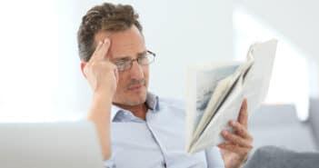 Ein Mann schaut mit kritischem Blick auf die Zeitung und kann nicht fassen, was er da liest