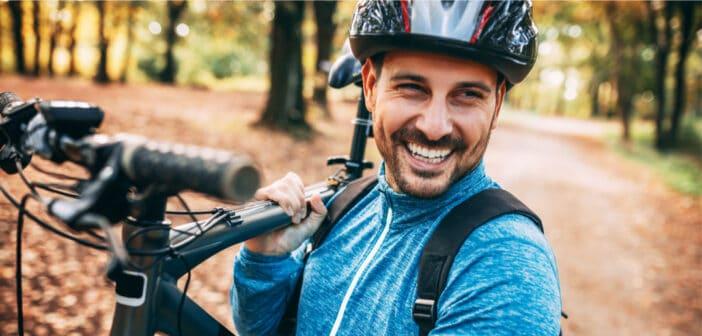 Ein Mann hat im Wald sein Mountainbike auf den Schultern und lächelt zufrieden in die Kamera