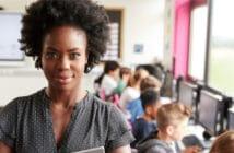 eine junge Lehrerin schaut in die Kamera, im Hintergrund ihre Klasse. Sie ist stolz, dass sie ihren Weg gegangen ist.