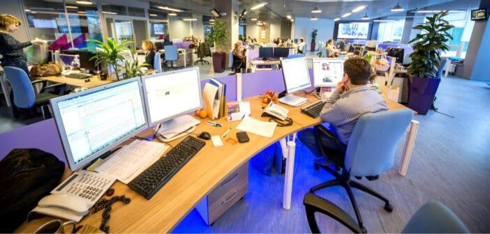 ein Mann sitzt im Newsroom am Schreibtisch