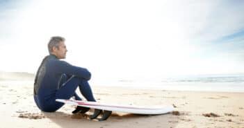 ein Mann sitzt am Strand mit seinem Surfbrett neben sich. Er schaut nachdenklich in die Ferne