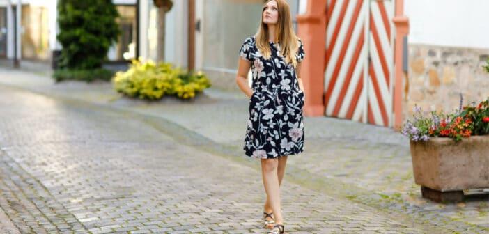 eine junge Frau spaziert durch eine Stadt und schaut sich um. Sie trägt ein Sommerkleid und offene Schuhe