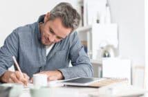 ein Mann sitzt am Schreibtisch mit Unterlagen auf dem Tisch und macht Notizen