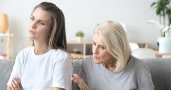 Die Mutter diskutiert mit der Tochter. Die Tochter sitzt mit dem Rücken zu ihr und hat ihr Arme verschränkt