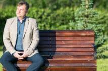 ein Mann sitzt auf einer Bank und schaut nachdenklich in die Ferne
