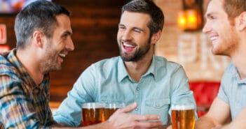 3 Männer sitzen in einer Bar und trinken ein Bier