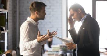 Der Chef und sein Mitarbeiter stehen sich gegenüber. Der Chef gestikuliert und der Mitarbeiter schaut verzweifelt auf ein Blatt Papier