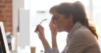 Eine Frau sitzt am Schreibtisch und hat die Brille in der Hand und die andere Hand vor dem Gesicht. Sie sieht verzweifelt aus
