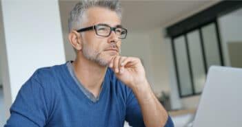 ein Mann sitzt am Schreibtisch und hat einen nachdenklichen Blick