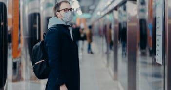 Ein Mann steht mit Maske an einem Bahngleis und wartet auf den Zug