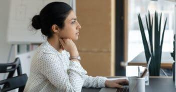 eine Frau schaut nachdenklich aus dem Fenster und sitzt am Schreibtisch